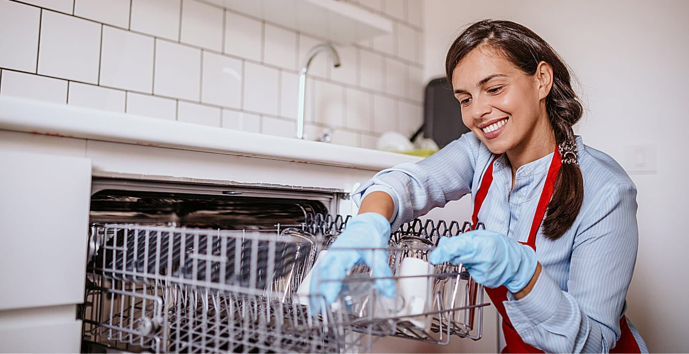 smiling woman wearing gloves and cleaning the inside of a dishwasher