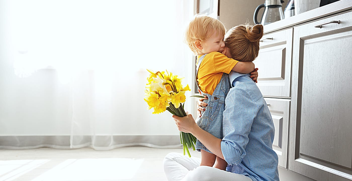 mom with her son holding yellow flowers and sitting on the kitchen floor