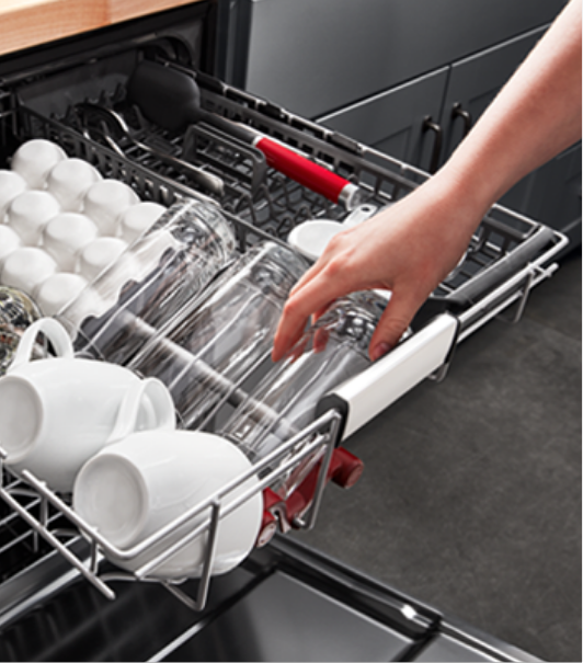 hand removing clean dishes from dishwasher