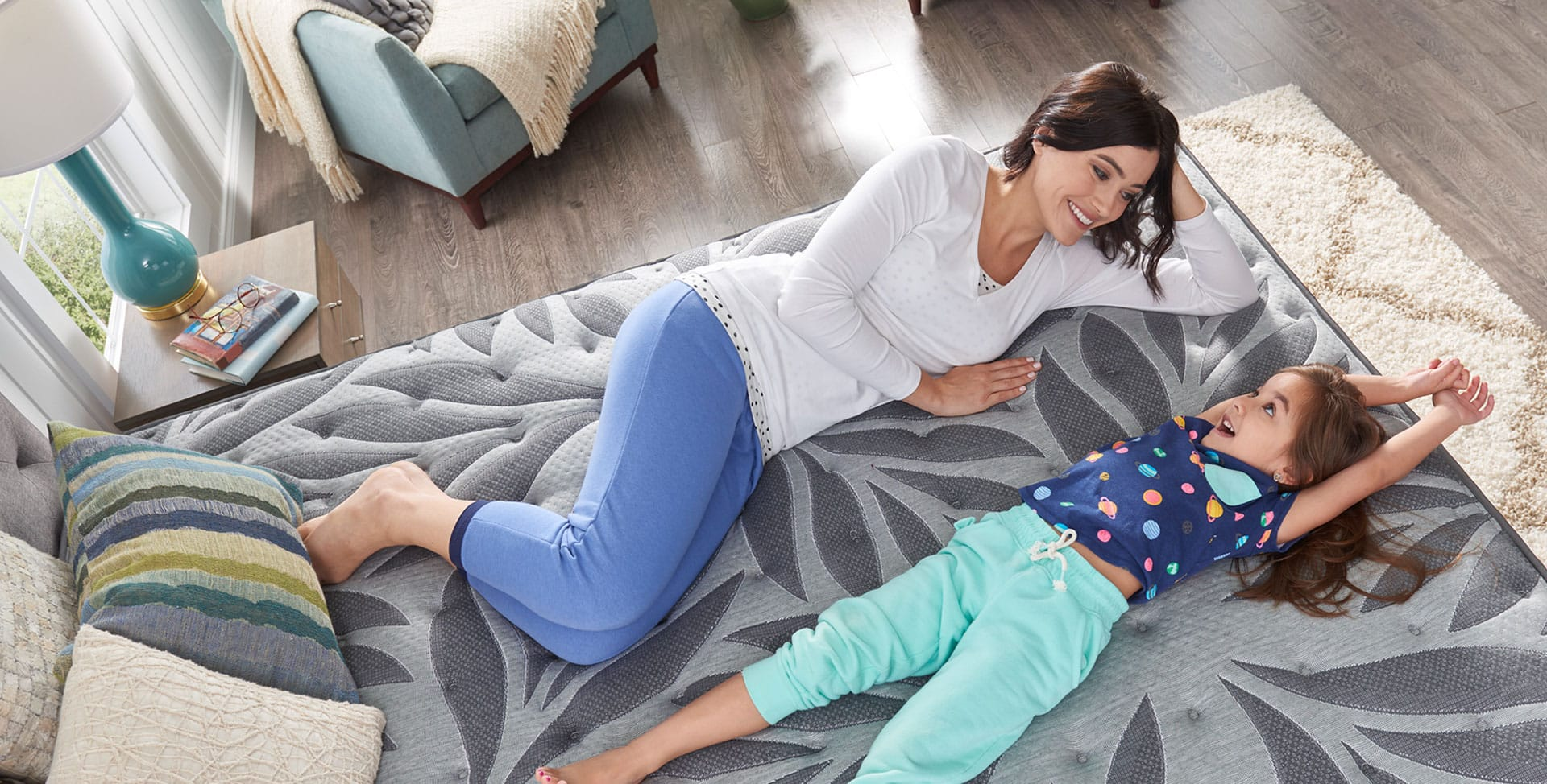 Mom and daughter lying on a Sealy<sup>®</sup> mattress